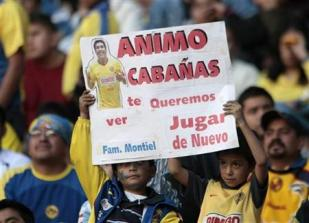 Club America's fans hold a poster with an image of soccer player Salvador Cabanas of Paraguay before their Mexican league championship soccer match between America and Indios in Azteca stadium in Mexico City January 31, 2010. REUTERS/Henry Romero